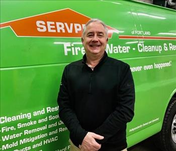 Male smiling in front of green SERVPRO van