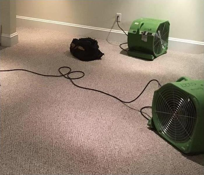 Two air movers placed on carpet drying up affected area after water damage