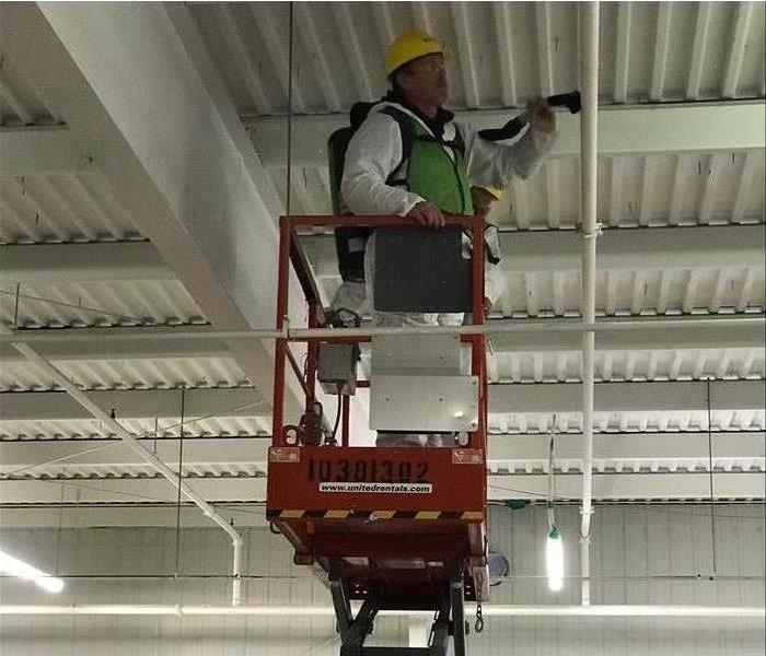 employee on lift cleaning ceiling