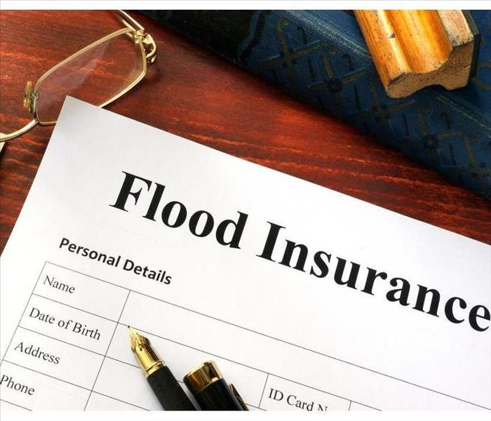 flood insurance document with glasses and a pen